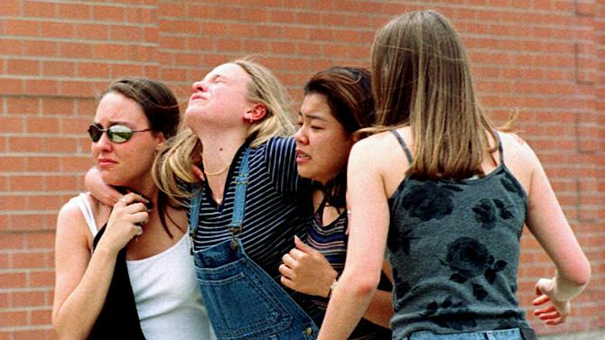 FILE - In this April 20, 1999, file photo unidentified young women head to a library near Columbine High School where students and faculty members were evacuated after two gunmen went on a shooting rampage in the school in the southwest Denver suburb of Littleton, Colo. Gun control advocates sputter at their own impotence. The National Rifle Association is politically ascendant. And Barack Obama's White House pledges to safeguard the Second Amendment in its first official response to the deaths of at least 12 innocents in a mass shooting at a new Batman movie screening in suburban Denver. Once, every highly publicized outbreak of gun violence produced strong calls from Democrats and a few Republicans for tougher controls on firearms. Now those pleas are muted, a political paradox that's grown more pronounced in an era scarred by Columbine, Virginia Tech, the wounding of a congresswoman and now the shootings in a suburban movie theater where carnage is expected on-screen only. (AP Photo/Kevin Higley, File)