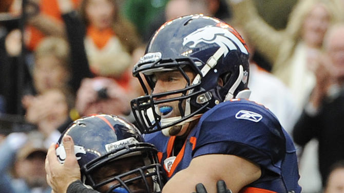 Denver Broncos quarterback Tim Tebow (15) and offensive tackle Ryan Clady (78) celebrate after Tebow scored a touchdown against the San Diego Chargers in the fourth quarter during an NFL football game, Sunday, Oct. 9, 2011, in Denver.  (AP Photo/Jack Dempsey)