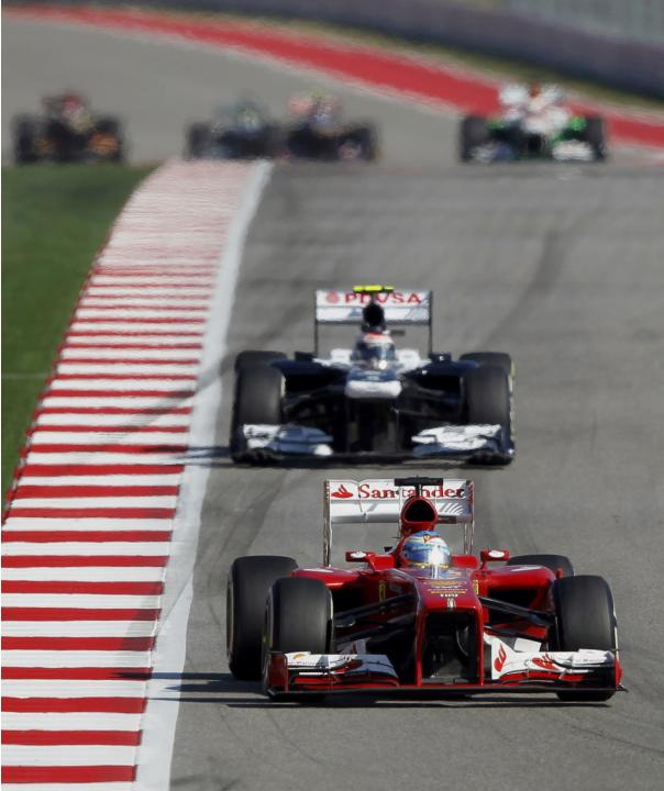 Fernando Alonso of Spain drives ahead of Valtteri Bottas of Finland during the Austin F1 Grand Prix at the Circuit of the Americas in Austin