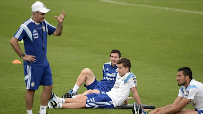 """Argentina's coach Alejandro Sabella (L) talks to his players forward Lionel Messi (C), midfielder Fernando Gago (2ndR) and defender Ezequiel Garay during a training session at """"Cidade do Galo"""" in Vespasiano on July 2, 2014"""