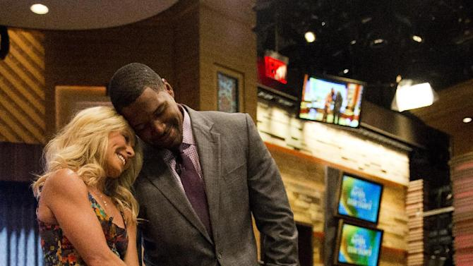 "Former football player Michael Strahan, right, is shown with Kelly Ripa on the set of the newly named ""Live! with Kelly and Michael"" on Tuesday, Sept. 4, 2012 in New York. Strahan joined the popular morning show as a permanent co-host on Tuesday, fulfilling a joking prophecy he made to Regis Philbin more than four years ago. The gap-toothed former New York Giant jogged onto the morning show set and picked up co-host Kelly Ripa in a bear hug, lifting her off her feet. He replaces Philbin, who left last November. Strahan was the survivor in a series of on-air tryouts of potential co-hosts since Philbin left, and his hiring has been an open secret for the past two weeks. (Photo by Charles Sykes/Invision/AP Images)"