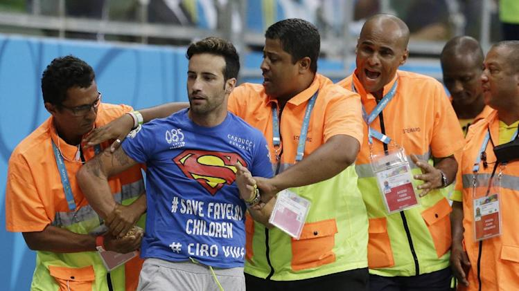 Stewards apprehend a man who ran onto the pitch during the World Cup round of 16 soccer match between Belgium and the USA at the Arena Fonte Nova in Salvador, Brazil, Tuesday, July 1, 2014. (AP Photo/Matt Dunham)