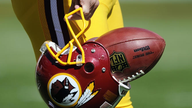 "In this Sept. 23, 2012, file photo, Washington Redskins punter Sav Rocca carries a football in his helmet before an NFL football game against the Cincinnati Bengals in Landover, Md. The U.S. Patent Office ruled Wednesday, June 18, 2014, that the Washington Redskins nickname is ""disparaging of Native Americans"" and that the team's federal trademarks for the name must be canceled. The ruling comes after a campaign to change the name has gained momentum over the past year"