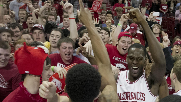 Arkansas' Jacorey Williams, right, and Anthlon Bell celebrate with fans after their 80-69 win over No. 2 Florida in an NCAA college basketball game in Fayetteville, Ark., Tuesday, Feb. 5, 2013. (AP Photo/Gareth Patterson)
