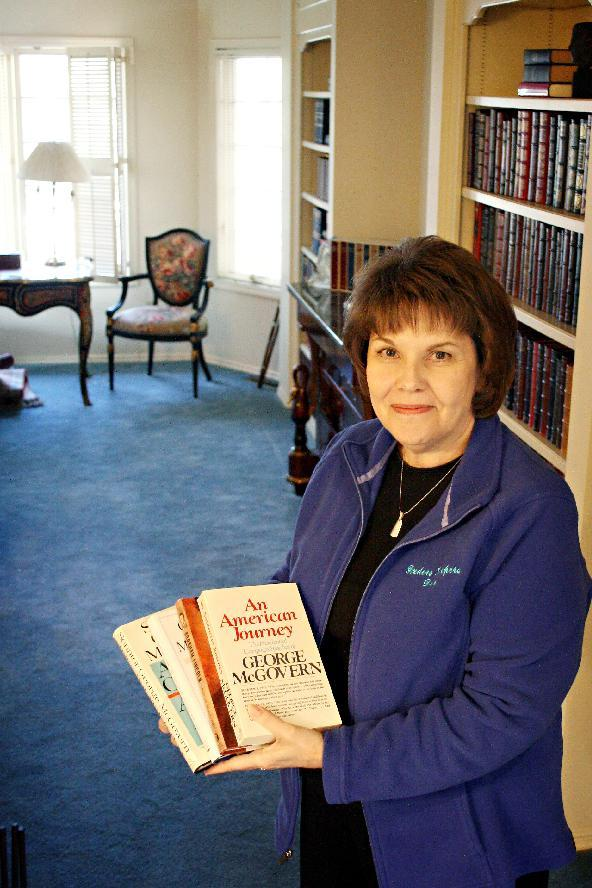 Deb Sorensen with Finders Keepers Estate, Collectable & Antique Sales shows off several books owned by former U.S. Sen. George McGovern in this Jan. 17, 2013, photo taken at his home in Sioux Falls, S.D. Items belonging to McGovern, who died in October at age 90, will be sold during the two-day sale at his Sioux Falls' home. The items include furniture, books, campaign material and personal photos. (AP Photo/Kristi Eaton)