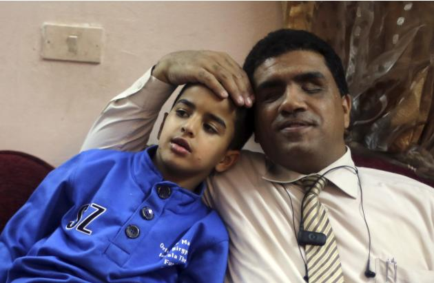 Blind lawyer Khaled Hanafy, who is married to Sherien Fathy, sits with his son Yehia at their home in Cairo