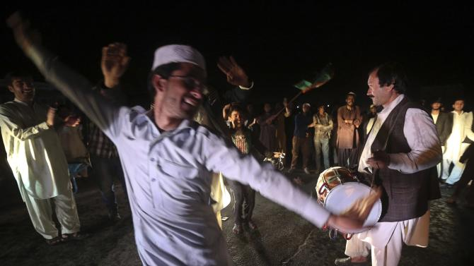 Supporters of Afghan presidential candidate Ashraf Ghani dance on the street after he was named president-elect in Kabul