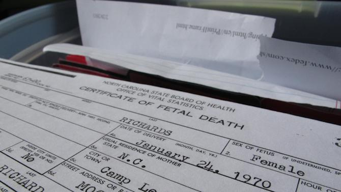 A certificate of fetal death sits atop a file box in the trunk of Mary Blakely's van parked at a cemetery in Jacksonville, N.C., on Wednesday, Feb. 27, 2013. The Marine's daughter scoured local cemeteries and death records for the names of children who may have died because of water contamination at nearby Camp Lejeune. (AP Photo/Allen Breed)