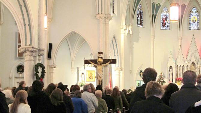 """This Jan. 12, 2014 photo shows people gathered for mass inside Our Lady of Perpetual Help Church in Buffalo, N.Y., during a """"Mass Mob."""" Borrowed from the idea of flash mobs, Mass Mobs encourage crowds to attend Mass at a specified church on a certain day to fill pews, lift spirits and help financially some of the city's oldest but often sparsely attended churches. (AP Photo/Carolyn Thompson)"""