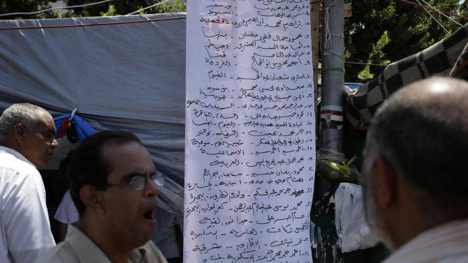 Supporters of Egypt's ousted President Mohammed Morsi check the names of people killed in clashes with security forces, outside a field hospital in Nasr City, Cairo, Egypt, Saturday, July 27, 2013. Clashes erupted early Saturday in Cairo between security forces and supporters of Egypt's ousted President Mohammed Morsi, killing scores of protesters and overwhelming field hospitals with the wounded, the Health Ministry said, in an outburst of violence that put the possibility of political reconciliation in the deeply divided nation ever further out of reach. Arabic banner lists the names of some of the dead. (AP Photo/Hassan Ammar)