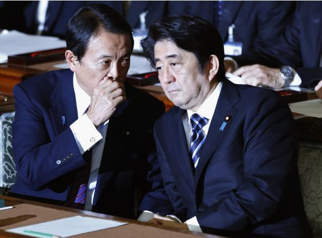 Japan's Prime Minister Abe listens to Deputy Prime Minister and Finance Minister Aso during the plenary session of the Lower House of the parliament as it rejects a no-confidence resolution agains