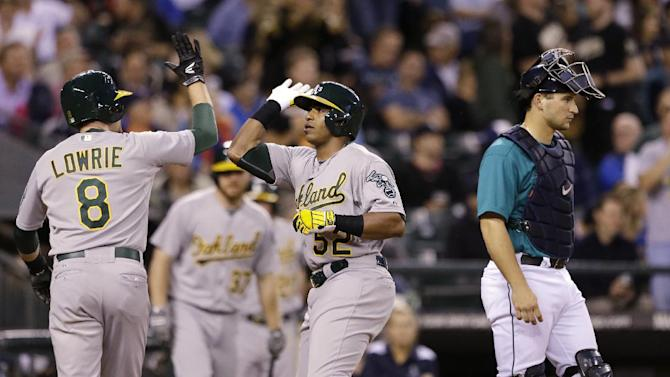 Seattle Mariners catcher Mike Zunino, right, waits for play to resume as Oakland Athletics' Jed Lowrie (8) greets Yoenis Cespedes at home on Cespedes' two-run home run in the ninth inning of a baseball game Friday, June 21, 2013, in Seattle. (AP Photo/Elaine Thompson)