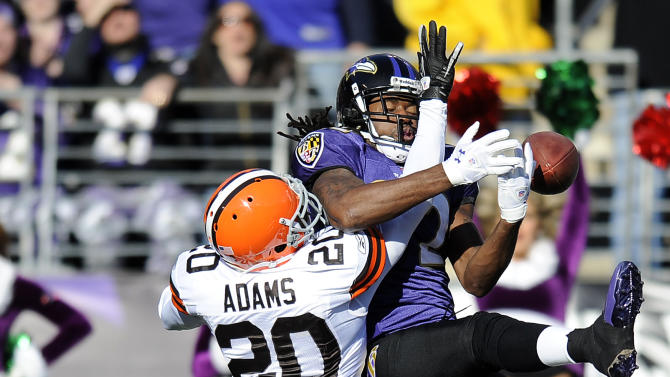 Cleveland Browns free safety Mike Adams (20) gets tangled with Baltimore Ravens wide receiver Torrey Smith as Smith goes up for a catch in the first half of an NFL football game in Baltimore, Saturday, Dec. 24, 2011. Cleveland was charged with a pass interference penalty on the play. (AP Photo/Nick Wass)
