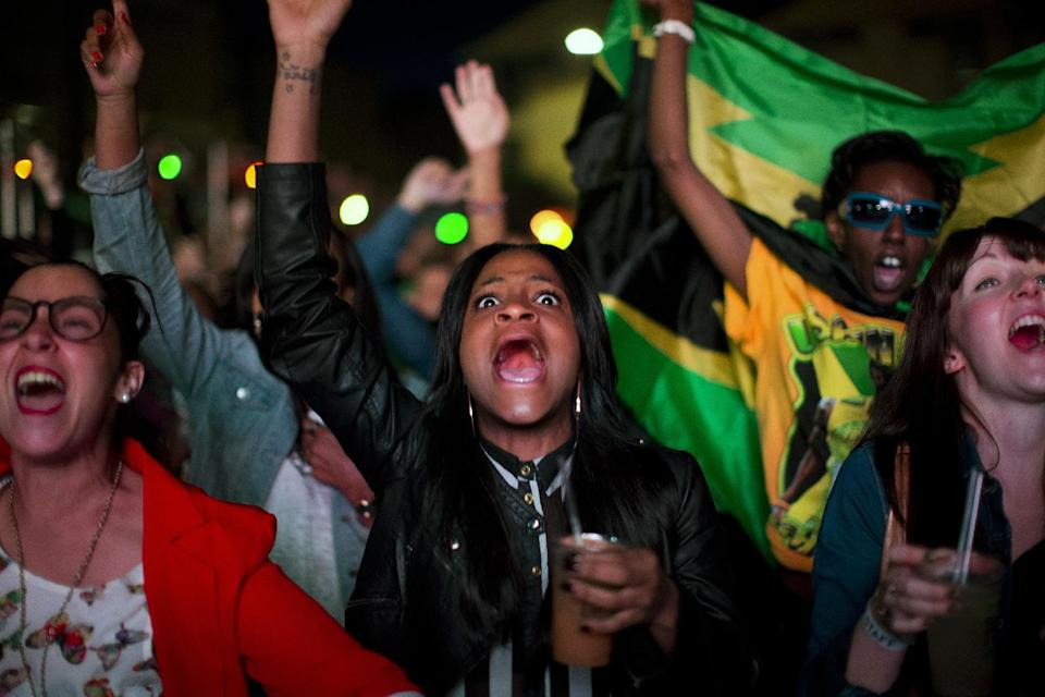 In this Sunday, Aug. 5, 2012 photo, Jamaica supporters cheer during a broadcast of the the men's 100-meter final on a screen at the Puma Yard in London during the 2012 Summer Olympics. (AP Photo/Emilio Morenatti