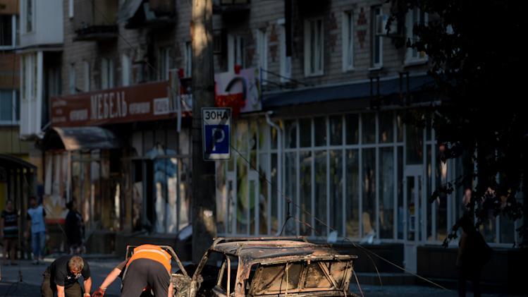 Officials remove a corpse from a burned car in downtown Donetsk, eastern Ukraine on August 27, 2014
