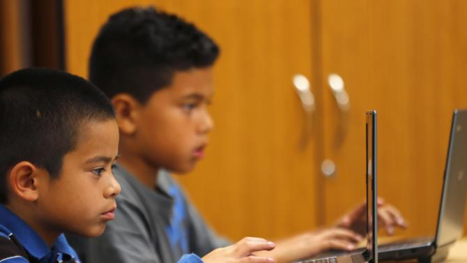 Grade four students work on laptop computers at Monarch School in San Diego, California
