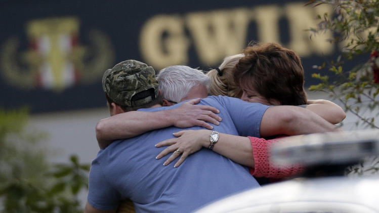 A group of people huddle together after an explosion and gunshots were heard near the scene where a man was holding four firefighters hostage Wednesday, April 10, 2013 in Suwanee, Ga. A police spokesman said the suspect was dead and none of the hostages suffered serious injuries.  (AP Photo/John Bazemore)