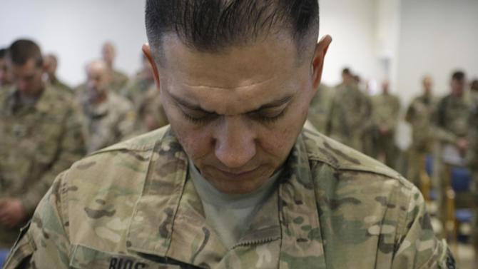 U.S. soldier, Rolando G. Rios, observes a moment of silence during a ceremony marking the 11th anniversary of the Sept. 11 attacks that killed almost 3,000 in the United States, at NATO camp Kaia in Kabul, Afghanistan, Tuesday, Sept. 11, 2012. (AP Photo/Musadeq Sadeq)