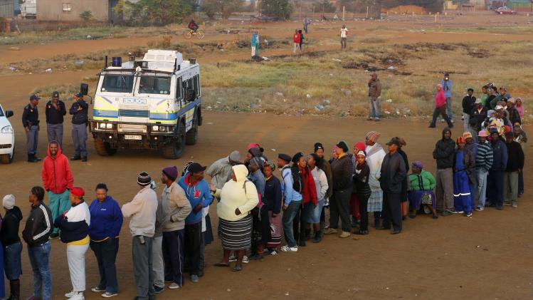 Police stand guard as voters queue to cast their ballots in Bekkersdal near Johannesburg