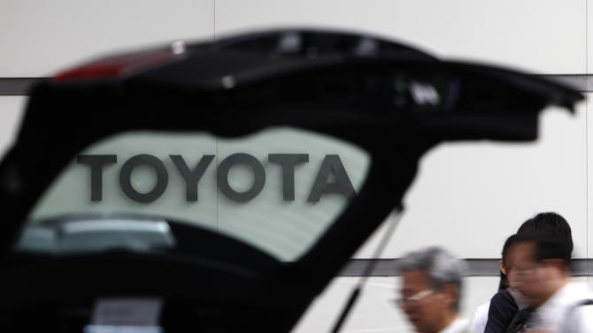 FILE - In this Aug. 2, 2011 file photo, people walk by a car on display at Toyota's Tokyo, Japan, headquarters. Toyota Motor Corp. said Wednesday it is recalling about 550,000 vehicles worldwide _ mostly in the United States _ for problems that could make it harder to steer. (AP Photo/Shizuo Kambayashi, File)