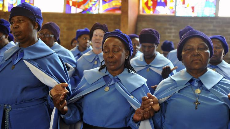Women pray during a service for the late former South African President Nelson Mandela at the Regina Mundi Church in Soweto