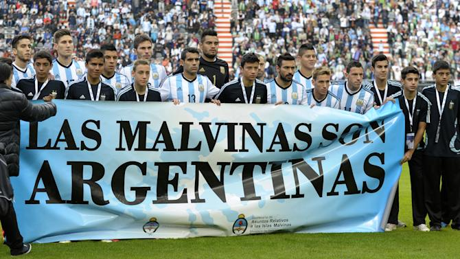 "Argentina's footballers hold a banner reading ""The Malvinas / Falkland Islands are Argentine"" before a friendly against Slovenia at La Plata stadium in La Plata, Buenos Aires, Argentina on June 7, 2014"