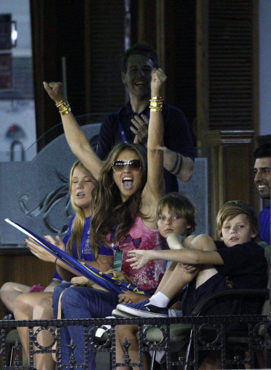 British actress and model Elizabeth Hurley, center, cheers a boundary by Rajasthan Royals captain Shane Warne, unseen, during an Indian Premier League (IPL) cricket match between Kings XI Punjab and R