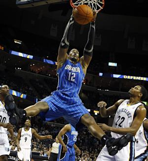 FILE - This Jan. 31, 2011 file photo shows Orlando Magic's Dwight Howard, center, dunking over Memphis Grizzlies teammates Darrell Arthur, left, and Rudy Gay, right,  during the first half of an NBA basketball game in Memphis, Tenn. Howard's departure from Orlando is nearly complete. The All-Star center could be a member of the Los Angeles Lakers as soon as Friday, Aug. 10, 2012, pending NBA approval of a four-team, eight-player trade also involving Denver and Philadelphia. (AP Photo/ Mark Weber, File)
