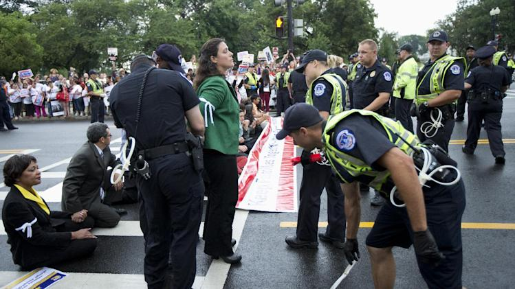 Capitol Hill police officers arrest immigration reform protestors as they blocked a street on Capitol Hill in Washington, Thursday, Aug. 1, 2013. (AP Photo/Manuel Balce Ceneta)