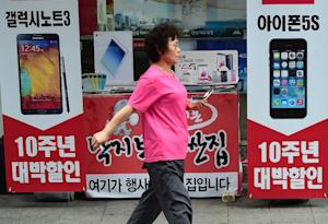 A woman walks past adverts for Samsung's Galaxy…
