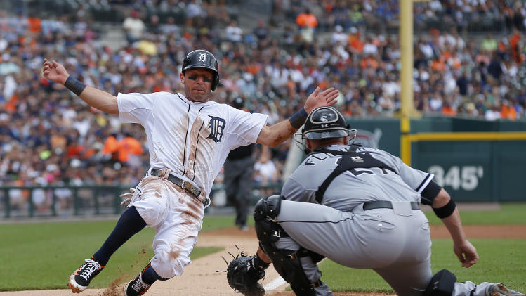 Detroit Tigers' Ian Kinsler slides into home plate as Chicago White Sox catcher Tyler Flowers (21) waits to make the tag in the first inning of a baseball game in Detroit, Thursday, July 31, 2014. Kinsler was out. (AP Photo/Paul Sancya)