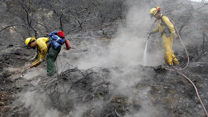Eric Smith, left and James Heaton, from San Diego work to clean up hotspots in the Angeles National Forest Wednesday Sept. 5, 2012 near Los Angeles. Fire crews are getting help from rain in battling a 3,800-acre fire in the San Gabriel Mountains northeast of Los Angeles.  (AP Photo/Nick Ut)