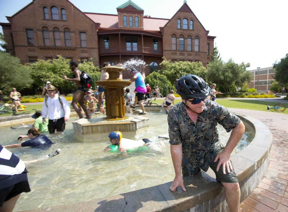 Mark Eastwood of Tempe, Ariz. gets out of the fountain in front of Old Main on the Arizona State University campus in Tempe during the Tempe Bicycle Action Group swimsuit ride on Saturday, June 29, 2013. About 100 cyclists biked around the city cooling off in pools and fountains. (AP Photo/The Arizona Republic, David Wallace)