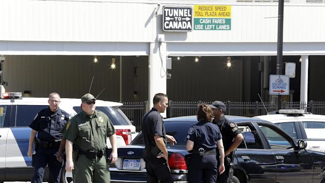 Authorities meet during a investigation of a bomb threat at the Detroit Windsor Tunnel Thursday, July 12, 2012. The tunnel was closed to traffic after the threat was called in on the Canadian side, tunnel chief executive Neal Belitsky told The Associated Press. The call was made some time after 12:30 p.m. to the duty free shop on a plaza on the tunnel's Windsor side, tunnel executive vice president Carolyn Brown said. The underwater tunnel stretches about a mile beneath the Detroit River, which is one of North America's busiest trade crossings. (AP Photo/Paul Sancya)