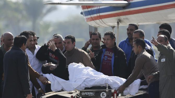 Former Egyptian President Hosni Mubarak waves to his supporters from his stretcher as he returns to Maadi military hospital in Cairo