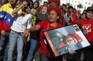 Supporters of Venezuela's late President Hugo Chavez protest over others cutting the line as they wait to view his body in state at the Military Academy in Caracas, March 7, 2013. Venezuelans flocked to pay tribute to Chavez two days after he died of cancer. REUTERS/Tomas Bravo