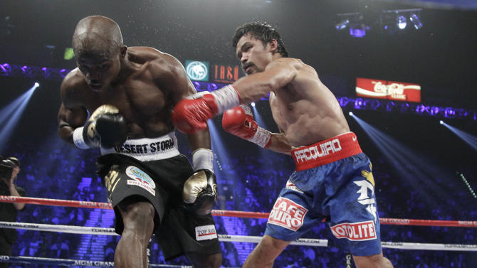 Manny Pacquiao, from the Philippines, right, connects with a punch against Timothy Bradley, from Palm Springs, Calif., in the third round of their WBO welterweight title fight Saturday, June 9, 2012, in Las Vegas. (AP Photo/Julie Jacobson)