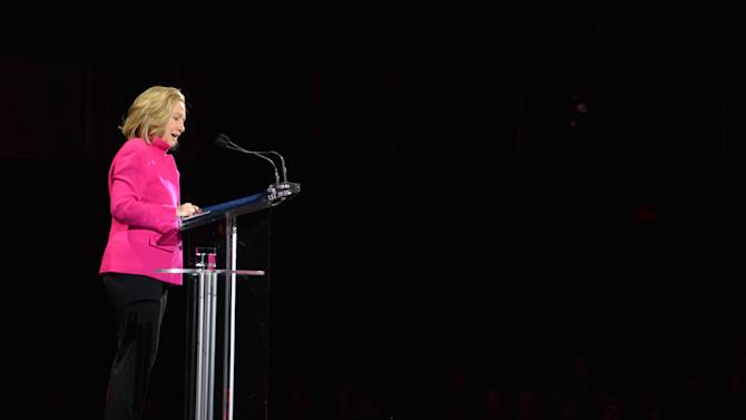 """This image released by Women in the World shows former Secretary of State Hillary Rodham Clinton  speaking at the Women in the World Conference on Friday, April 5, 2013 in New York. Clinton said Friday that the rights of women represent """"the unfinished business of the 21st century"""" in the United States and around the world, receiving a rapturous reception for one of her first speeches since departing the Obama administration.  (AP Photo/Women in the World, Marc Bryan-Brown)"""