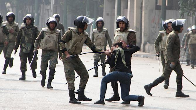 """FILE - In this Friday, Dec. 16, 2011 file photo, Egyptian army soldiers arrest a woman protester during clashes with military police near Cairo's downtown Tahrir Square. Amnesty International warned Tuesday that the practice of impunity for Egyptian police and military continued even after regime change and Hosni Mubarak's ouster, and urged the country's newly elected leader to deal with this """"bloody legacy"""" by bringing to justice those responsible for killing, maiming and abusing protesters. (AP Photo, File)"""