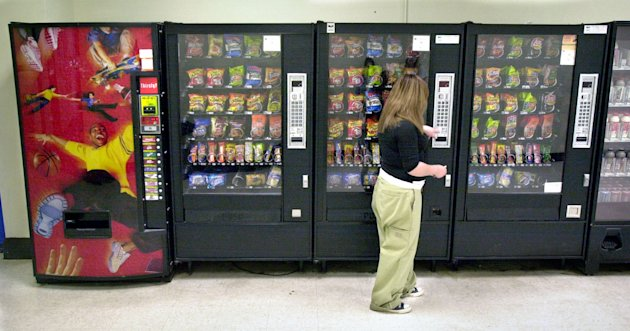 In this May 3, 2006 photo, a student purchases a brown sugar Pop-Tart from a vending machine in the hallway outside the school cafeteria, in Wichita, Kan. According to the first large study of states laws governing the sale of junk food and drinks in U.S. public schools, these regulations may help curb childhood obesity. (AP Photo/The Wichita Eagle, Mike Hutmacher)