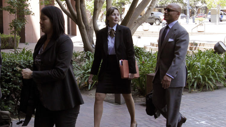 Judy Clarke, the lawyer representing shooting suspect Jared Lee Loughner, second from right, talks with lawyer Reuben Cahn, right, as she makes her way towards a federal courthouse Friday, Aug. 26, 2011, in San Diego. Attorneys for the Tucson shooting rampage suspect are making another attempt to stop the forced medication of their client at the Missouri prison facility where mental health experts are trying to make him psychologically fit to stand trial. (AP Photo/Gregory Bull)