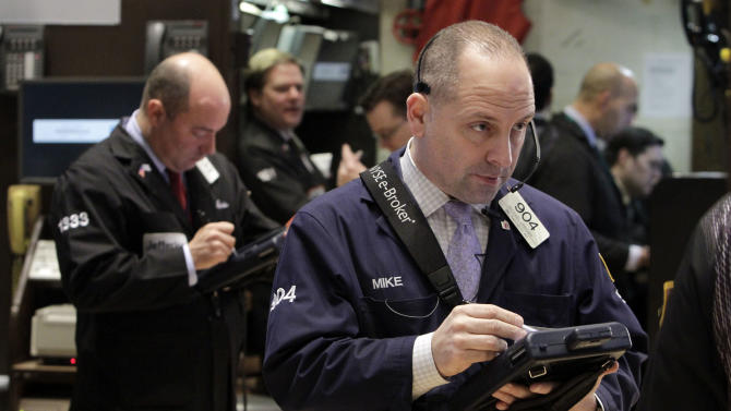 Michael Urkonis, right, works with fellow traders on the floor of the New York Stock Exchange, Friday, March 9, 2012. Stocks rose Friday morning after the February jobs report bolstered hopes that the economic recovery is on track. (AP Photo/Richard Drew)
