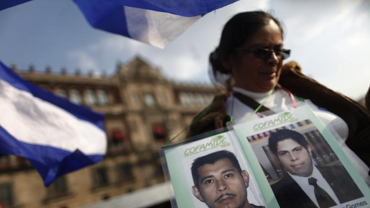A woman from the Caravan of Central American Mothers holds up photos of missing migrants during a march in front of the National Palace in Mexico City