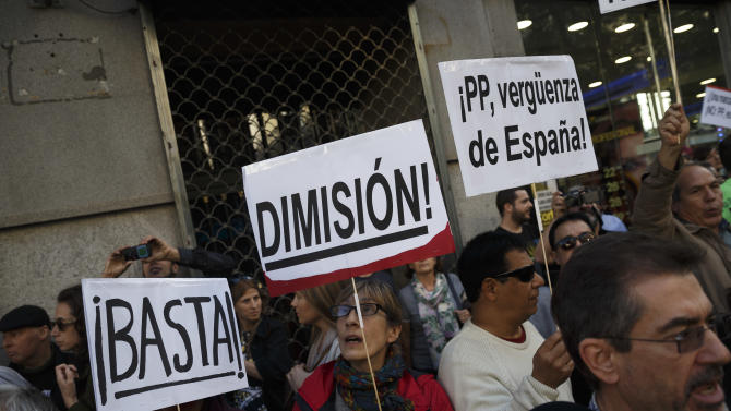 Protestors shout against corruption and hold banner reading 'Enough, Resign, PP Shame of Spain' during a demonstration in Madrid, Spain, Friday, April 17, 2015. Former Finance Minister and International Monetary Fund chief Rodrigo Rato said Friday April 17, 2015, he plans to cooperate with justice officials after being detained for several hours while investigative tax agents searched his apartment and an office in Madrid. A spokesman for Madrid's justice tribunal said Rato was under investigation by Madrid prosecutors for fraud, money laundering and asset concealment.(AP Photo/Daniel Ochoa de Olza)