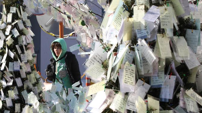 A woman passes by papers, bearing New Year wishes, tied to trees at  Myeongdong Catholic Cathedral in Seoul, South Korea, Monday, Dec. 31, 2102. The cathedral is Korea's oldest parish church and the symbol of Korean Catholics. (AP Photo/Ahn Young-joon)