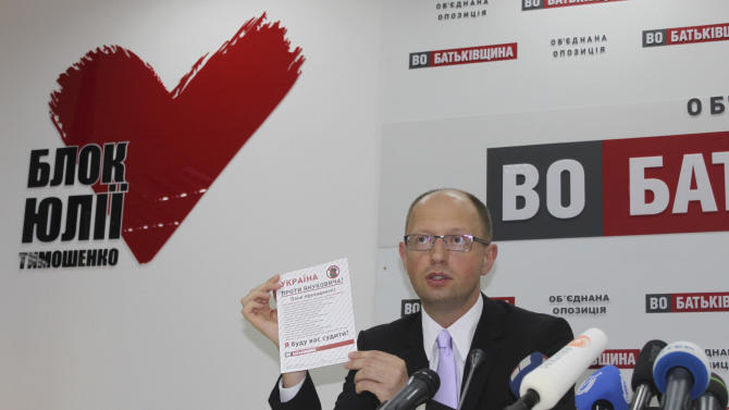 Ukraine's opposition leader Arseniy Yatsenyuk shows a petition calling for a lawsuit against President Viktor Yanukovych during a news conference on Monday July 16, 2012, in Kiev, Ukraine.  Three months ahead of a parliamentary election, Ukraine's opposition groups have launched a campaign to impeach President Viktor Yanukovych. (AP Photo/Maria Danilova)