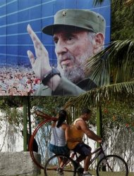 People ride a bicycle near a poster of former Cuban leader Fidel Castro in Havana March 26, 2012. Pope Benedict arrives in Cuba on Monday for a three-day visit that has fueled aspirations for deeper economic and political change on the communist-run island and which the Roman Catholic Church hopes will spark a faith revival. REUTERS/Enrique de la Osa