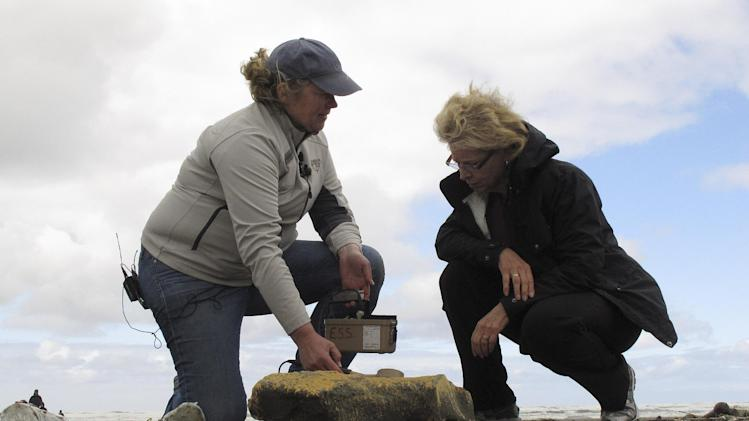 Washington Gov. Chris Gregoire, right, listens as Lynn Albin of the Department of Health describes the Geiger counter readings she's getting from a piece of styrofoam found on the beach in Ocean Shores, Wash., Monday, June 18, 2012. Officials say that there has been no radiation detected from items that have washed ashore. Gov. Gregoire announced Monday a state plan to address tsunami debris that reaches the state's coast from Japan but stressed that federal help is needed. (AP Photo/Rachel La Corte)