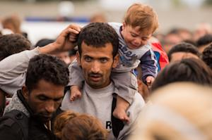 Migrants queue up for buses after they arrived at the…