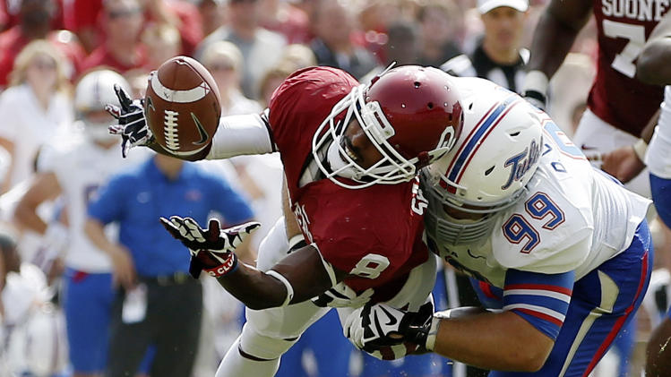 Oklahoma wide receiver Jalen Saunders (8) can't hold onto the pass as he is hit by Tulsa defender Derrick Luetjen (99) in the second quarter of an NCAA college football game in Norman, Okla., Saturday, Sept. 14, 2013